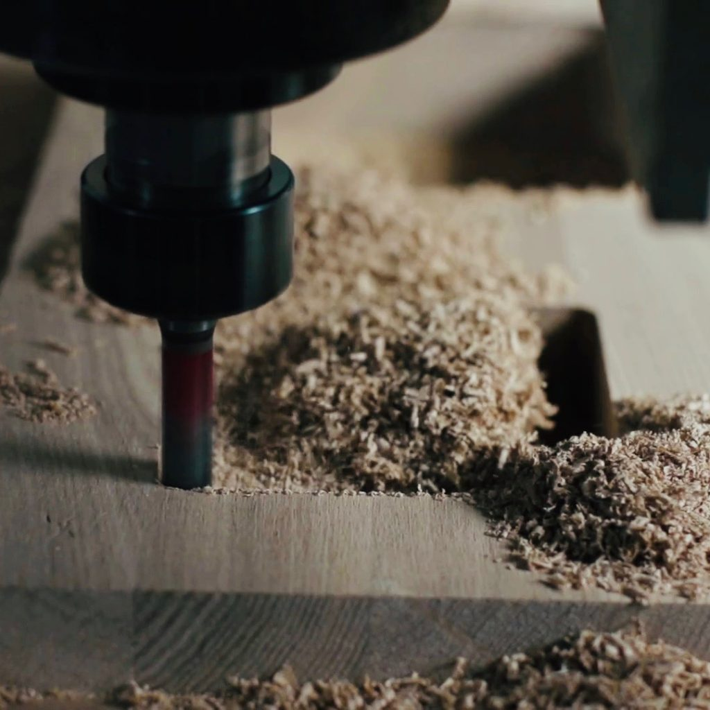 videoblocks-automatic-milling-cutting-wood-machine-drill-holes-for-the-pieces-of-wood-closeup-slowmotion-sawdust-fly-in-different-directions_hftvn4ojpl_thumbnail-full01